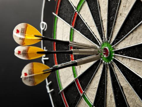 Drei Darts im Bullseye einer Dartsscheibe